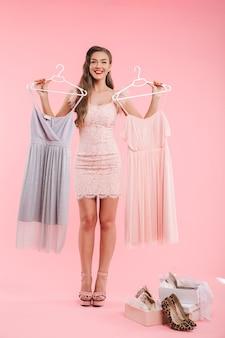 Photo pleine longueur de joyeuse jeune femme de 20 ans tenant deux robes sur des cintres et en choisissant lors de vos achats, isolé sur un mur rose