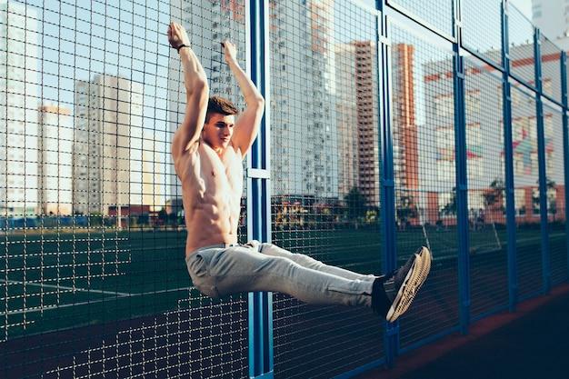 Photo pleine longueur d'un mec tendu avec un corps musclé nu à l'entraînement d'entraînement sur une clôture le matin sur le stade. il porte une culotte grise. il a l'air concentré.