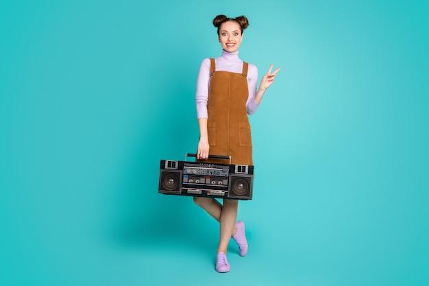Photo pleine longueur mignon attrayant deux jolis petits pains coiffure dame soirée disco à thème rétro tenir la main du joueur v-sign porter automne mini robe à la mode chaussures violettes pull isolé fond de couleur sarcelle