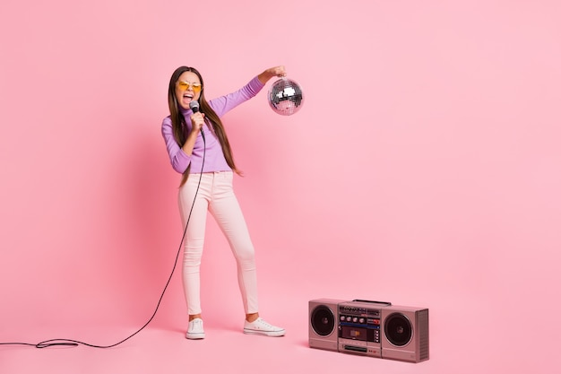 Photo pleine longueur d'une petite fille chanter une chanson avec un micro tenant une boule disco avec une boîte de boom isolée sur un fond de couleur pastel