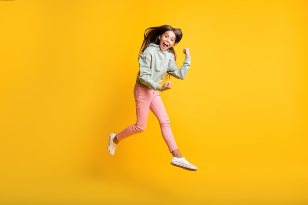 Photo pleine longueur de petites personnes sautent le poing vers le haut oui réalisation sweat à capuche à la mode isolé sur fond de couleur jaune