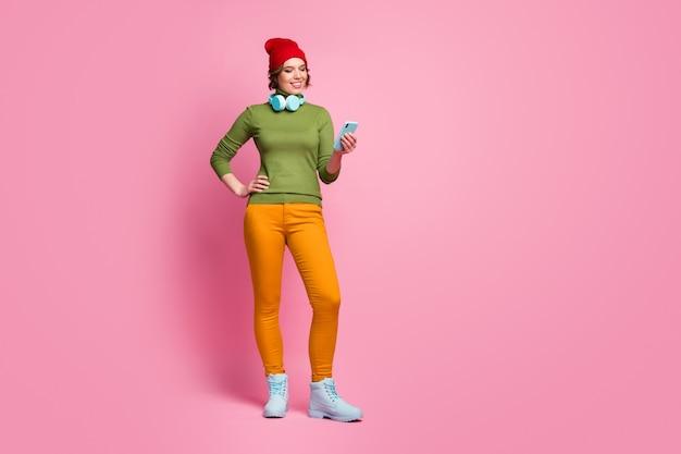 Photo pleine longueur positive fille joyeuse utiliser smartphone ont des écouteurs élégant cavalier recherche mélodie pistes en ligne porter des pantalons d'automne chaussures couvre-chef rouge isolé mur de couleur rose