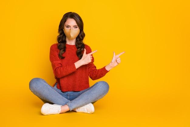Photo pleine longueur d'un promoteur de fille positif assis au sol, les jambes croisées, l'index pointé montrant les nouvelles covid porter un pull de masque médical rouge en denim isolé sur fond de couleur brillant brillant