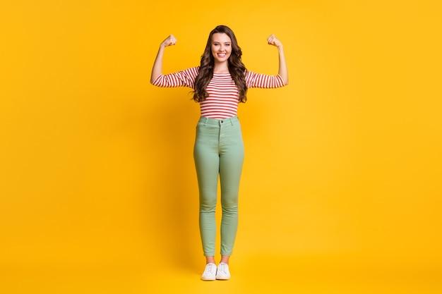 Photo pleine longueur de la taille du corps d'une fille montrant des biceps forts avec des cheveux longs souriant avec des mains isolées sur un fond de couleur jaune vif