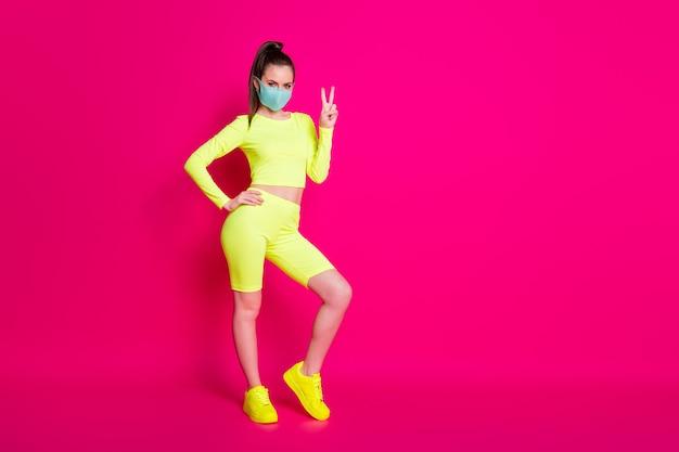 Photo pleine longueur de la taille du corps d'une fille portant des baskets de sport montrant un geste de signe v isolé sur un fond de couleur fuchsia lumineux