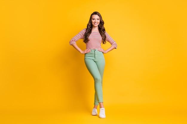Photo pleine longueur de la taille du corps d'une jolie fille aux cheveux longs portant des vêtements décontractés souriant isolé sur fond de couleur jaune vif