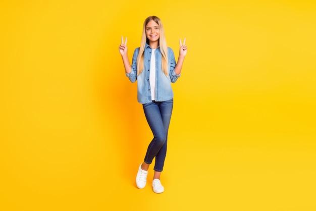 Photo pleine longueur de la taille du corps d'une préadolescente blonde souriant joyeusement montrant la démonstration du signe v avec les deux mains portant des vêtements en denim isolés sur un fond de couleur jaune vif