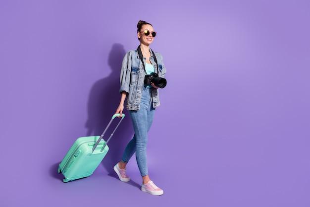 Photo pleine longueur de tourisme week-end de voyage fille tenir une valise porter un jean veste singulet