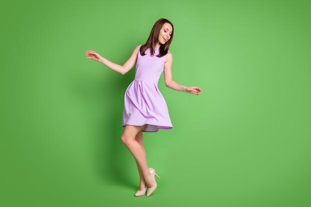 Photo pleine taille adorable douce fille insouciante dame regarder vers le bas côté mains robe de soirée de bal air coup jambes minces magasin de chaussures annonce concept porter robe violette isolé fond de couleur vert pastel