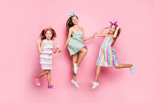 Photo pleine taille de beaux frères et sœurs sautant portant bandeau robe jupe lumineuse isolé sur fond rose