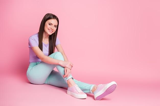 Photo pleine taille du contenu fille candide s'asseoir sur le sol profiter du week-end porter des vêtements de bonne apparence isolés sur fond de couleur rose