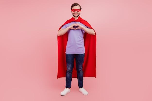 Photo pleine taille du jeune superman puissance forte spectacle doigt coeur signe amour isolé sur fond de couleur rose