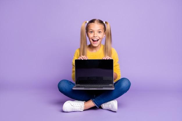 Photo pleine taille de l'enfant excité étonné montrer ordinateur portable écran tactile crier wow omg s'asseoir croisé les jambes pliées porter une tenue de style décontracté isolé sur un mur de couleur violette