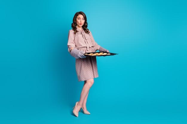 Photo pleine taille d'une femme au foyer surprise tenant un plateau de four faisant de délicieux biscuits portant des talons aiguilles à pois isolés sur fond de couleur bleu