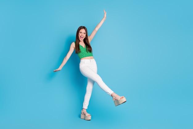 Photo pleine taille d'une fille folle assez candide lever la jambe de la main crier profiter de se réjouir le week-end d'été porter un débardeur isolé sur fond de couleur bleu
