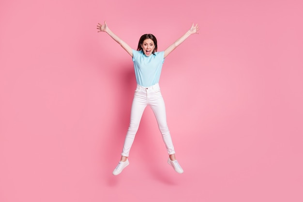 Photo pleine taille d'une fille folle étonnée sauter lever les mains star porter des détectives isolés sur fond de couleur rose