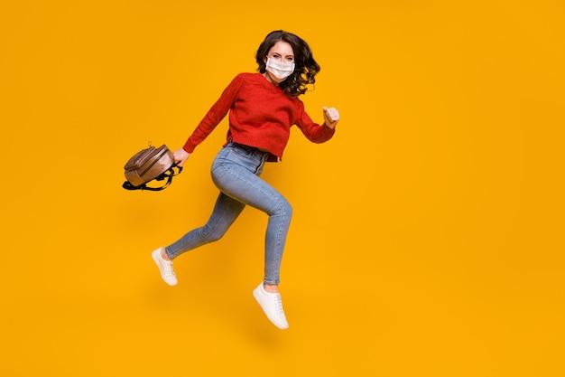 Photo pleine taille fille masque médical blanc saut aller marcher tenir sac à dos ne peut pas voyager week-end tournée covid-19 quarantaine porter pull rouge pull jean denim isolé fond de couleur brillant brillant