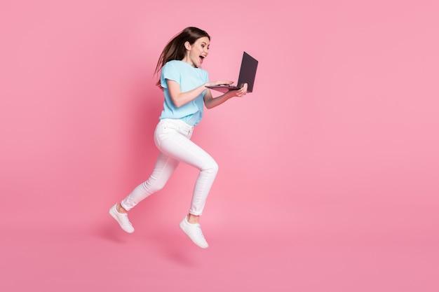 Photo pleine taille d'une fille qui saute sur un ordinateur portable en ligne avec des remises en t-shirt bleu pantalon pantalon isolé sur fond de couleur pastel