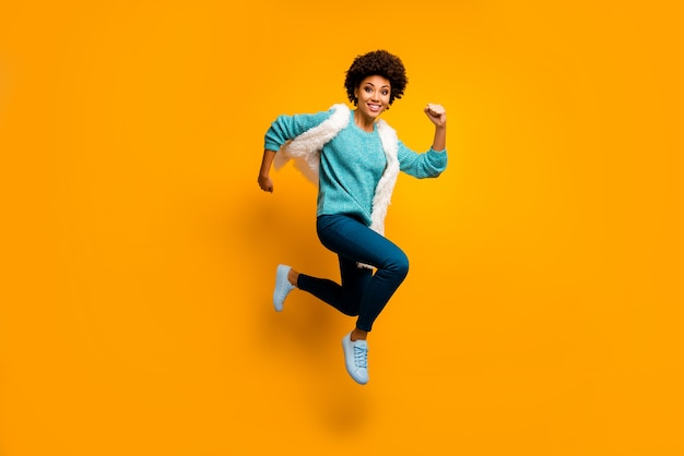 Photo pleine taille de folle drôle funky afro-américaine fille sauter courir dépêchez-vous de porter un pull blanc turquoise automne bleu élégant tenue à la mode isolée sur un mur de couleur jaune vif