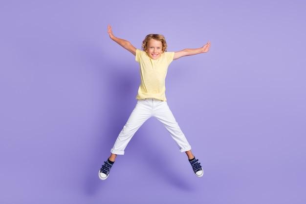 Photo pleine taille d'un garçon joyeux qui saute dans la main et porte des vêtements blancs jaunes isolés sur fond de couleur violette