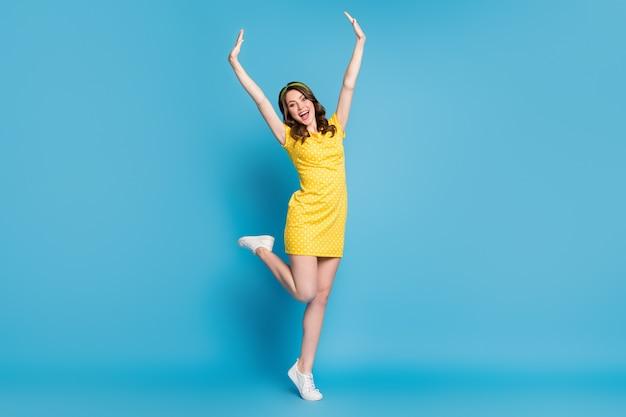 Photo pleine taille d'une jeune fille excitée lever les mains crier la jambe porter une jupe à pois isolée sur fond de couleur bleu