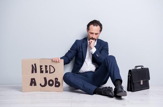 Photo pleine taille d'un perdant à l'esprit bouleversé licencié un homme mûr homme sans emploi tenir une pancarte en carton besoin de travailler s'asseoir au sol une mallette chercher un lieu de bureau porter des chaussures de costume isolées sur fond gris