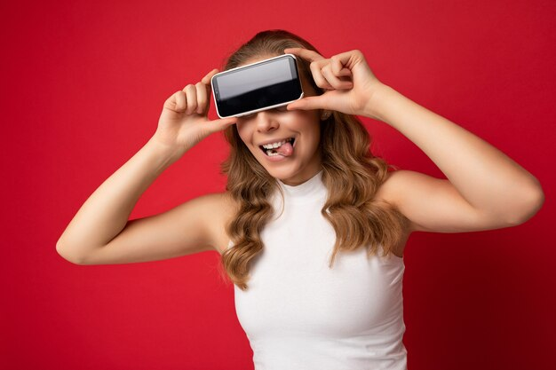 Photo de portrait d'une drôle de jeune femme blonde portant un t-shirt blanc isolé sur fond rouge avec un espace de copie tenant un smartphone montrant le téléphone à la main avec un écran vide pour la découpe et montrant la langue.
