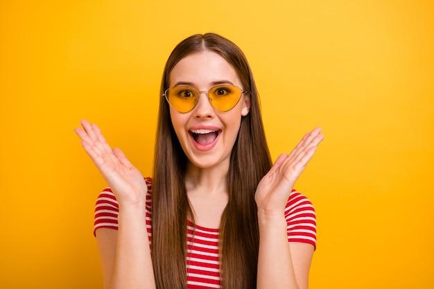 Photo de portrait en gros plan d'une belle jeune fille excitée, longue coiffure, bouche ouverte, lever les mains, paumes, face à une vente incroyable, porter des spécifications de soleil, chemise rouge blanche rayée, fond de couleur jaune vif