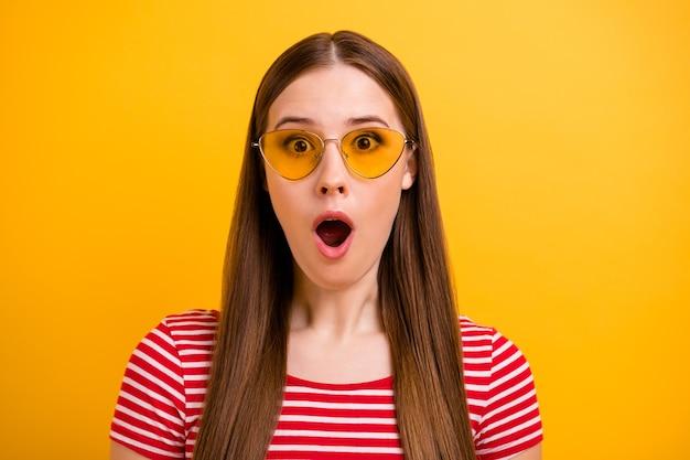 Photo de portrait en gros plan d'une jeune fille assez choquée, bouche ouverte, regardant des remises surprenantes, boutique de vente, vêtements de soleil, spécifications rayées, chemise rouge blanche, fond de couleur jaune vif