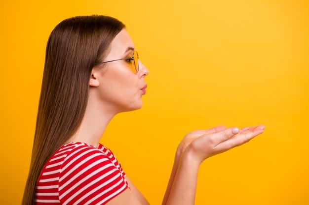Photo de portrait en gros plan d'une jolie jeune fille souffler des lèvres de paumes envoyer un baiser d'air intérêt romantique attirer un petit ami porter des spécifications de soleil chemise rouge blanche rayée fond de couleur jaune vif