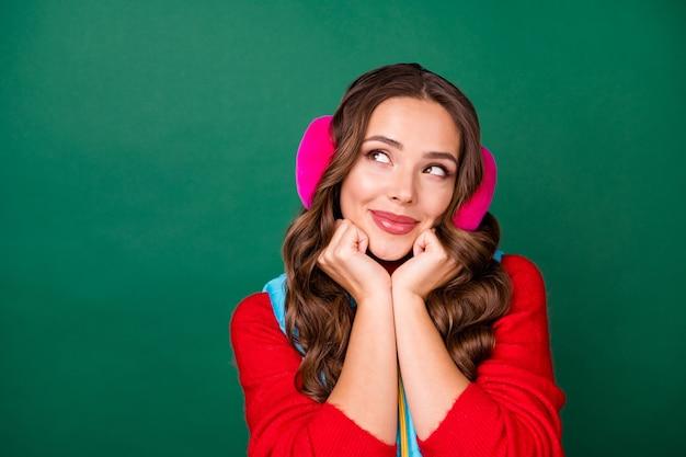 Photo de portrait en gros plan de jolies mains de jeune femme rêveuse charmante tenir le visage chercher un espace vide imaginer de futures vacances d'été porter des cache-oreilles roses pull rouge isolé fond de couleur verte