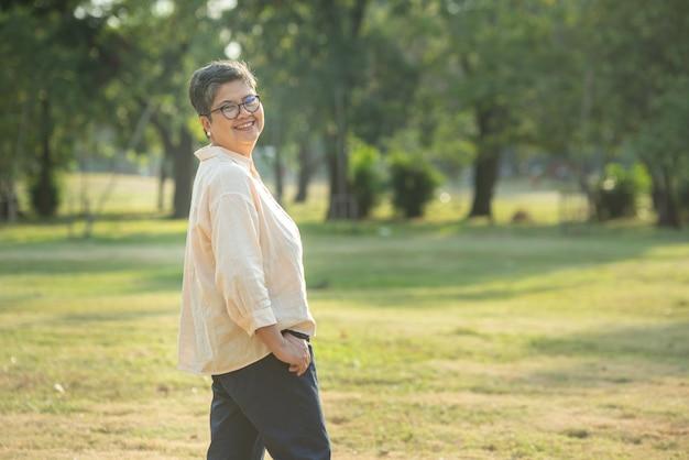 Photo portrait d'heureuse, réussie, se détendre caucasien senior femme asiatique souriant avec des lunettes et un regard insouciant vers la caméra dans le parc comme arrière-plan avec copie espace dans la lumière naturelle du soleil d'automne.