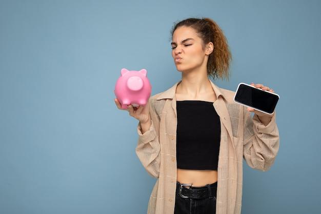 Photo portrait d'une jeune belle femme brune et bouclée insatisfaite et douteuse avec des émotions sincères portant une chemise beige élégante isolée sur fond bleu avec espace pour copie, détient un cochon rose