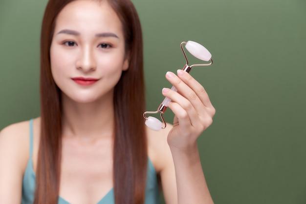 Photo portrait d'une jeune femme semblant utiliser détendue tout en utilisant un rouleau de visage en quartz rose naturel.