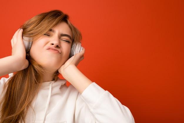 Photo de portrait d'une jolie jeune femme blonde positive émotionnelle portant un sweat à capuche blanc