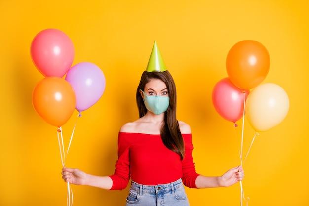 Photo positive fille masque médical profiter de la célébration de l'anniversaire festif quarantaine covid tenir des ballons porter des jeans en denim de style élégant à cône haut rouge isolé fond de couleur brillant brillant