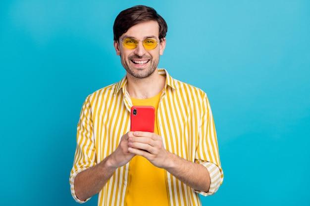 Photo positive guy homme voyageur utiliser un smartphone profiter de textos en tapant poster un commentaire s'abonner suivre les blogueurs de voyage portent une tenue jaune blanche isolée fond de couleur bleu
