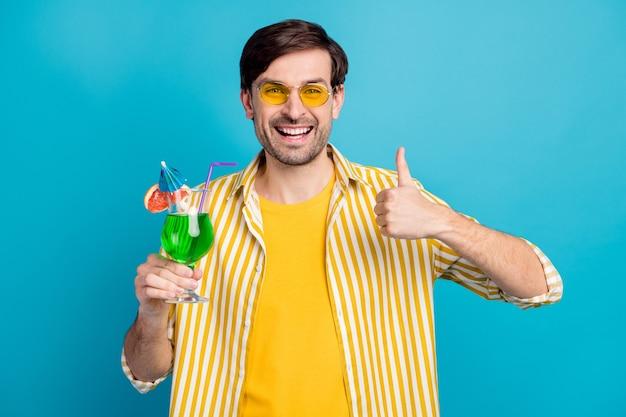 Photo positive joyeux voyageur de gars profiter d'un voyage exotique tenir un cocktail en verre approuver un spectacle de boissons signe de pouce porter une chemise jaune blanche à rayures isolée sur fond de couleur bleu