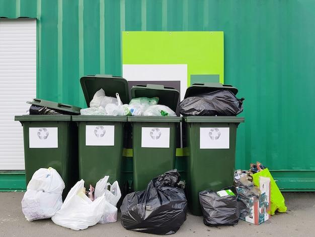 Photo de poubelles sacs poubelles près de la clôture verte