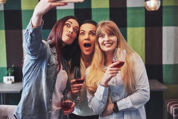 Photo présentant un groupe d'amis heureux avec du vin rouge prenant selfie