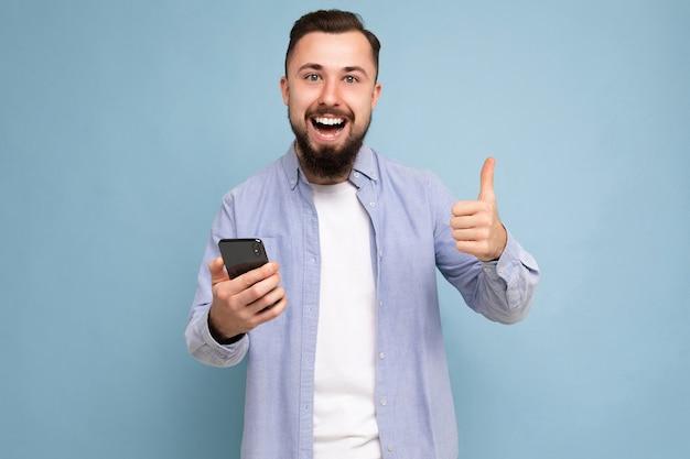 Photo prise de beau positif barbu beau jeune homme portant une tenue élégante décontractée en train de se poser
