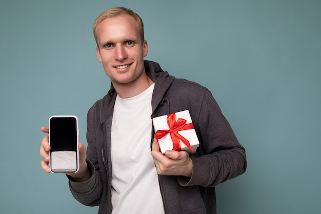 Photo prise de beau sourire heureux jeune homme blond isolé sur fond bleu mur portant