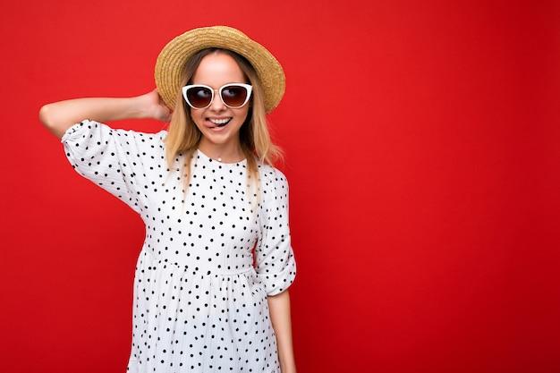 Photo prise de belle jeune femme blonde positive portant des vêtements décontractés d'été