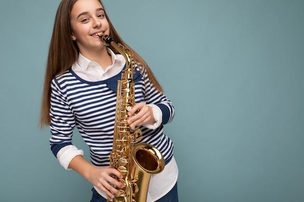 Photo prise de belle petite fille brune souriante et souriante portant des rayures à manches longues debout