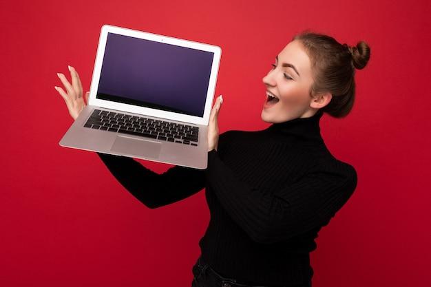 Photo prise de belle souriante heureuse surprise étonnée choquée jeune femme aux cheveux noirs tenant