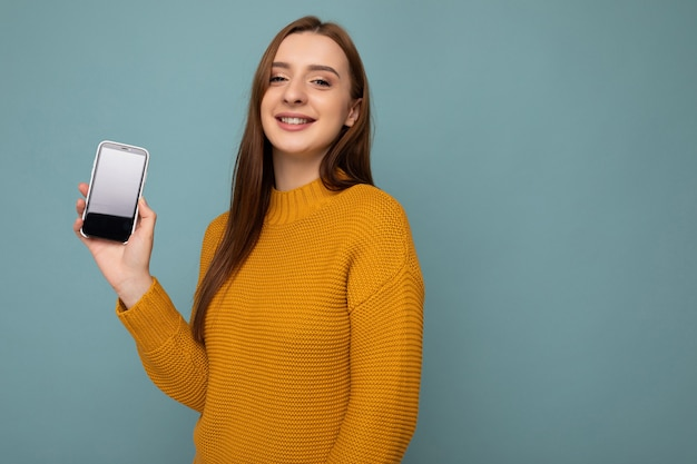Photo prise de jolie jeune femme positive portant un chandail orange en équilibre isolé sur bleu