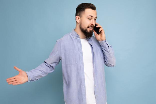 Photo prise de photo de beau jeune homme barbu brunet portant chemise bleue décontractée et t-shirt blanc