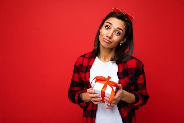 Photo prise de photo de jolie jeune femme brune positive isolée sur un mur rouge portant du blanc