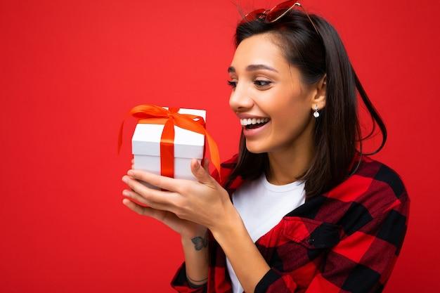 Photo prise de photo de jolie jeune femme brune souriante positive isolée sur fond rouge portant le mur