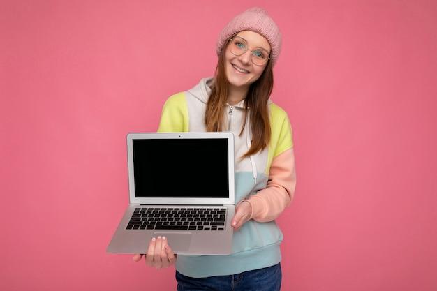 Photo prise de vue de sourire jolie jeune femme portant un chapeau et des lunettes tenant un ordinateur portable portant des écouteurs blancs regardant la caméra isolée sur fond rose. maquette